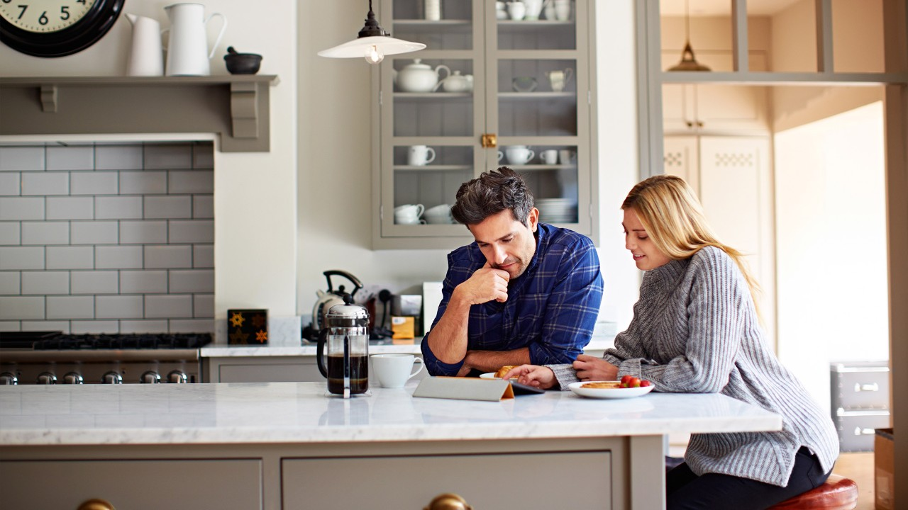 Couple using digital tablet in the kitchen