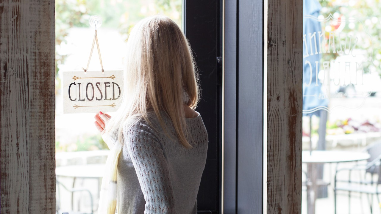 Woman turning sign close in shop window