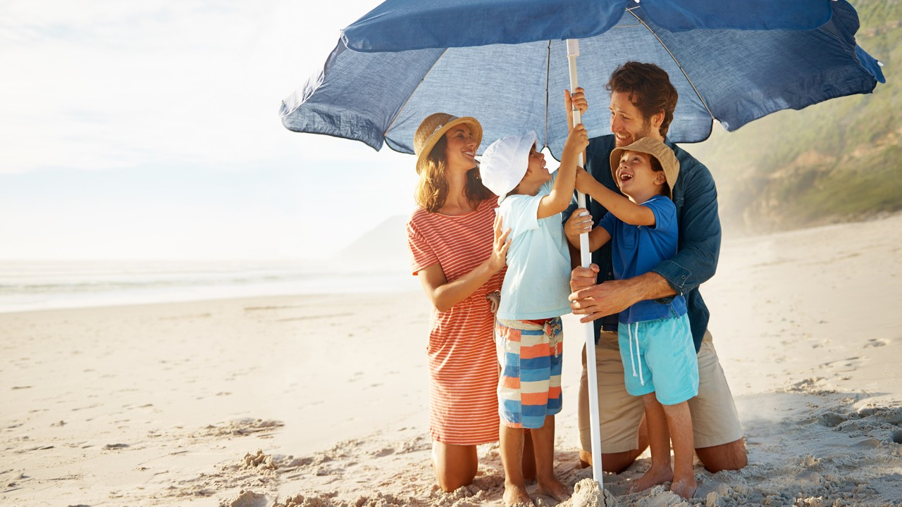 Family on the beach under umbrella