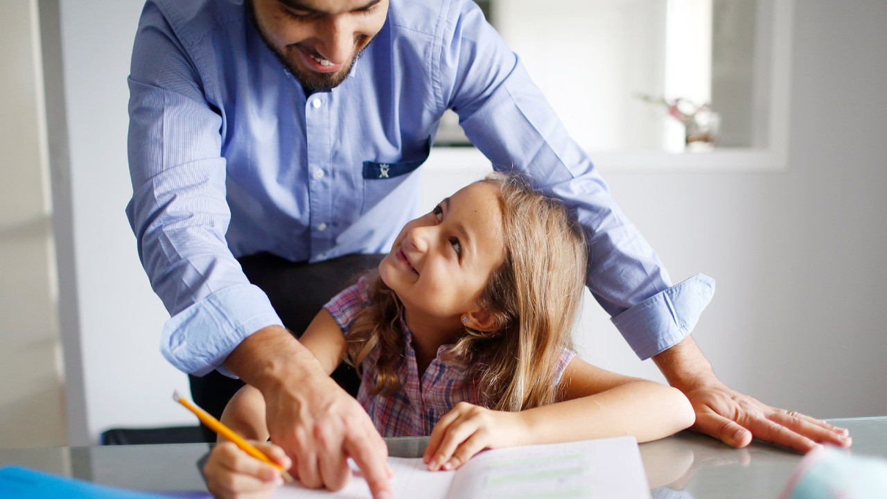 Father helps his daughter with homework