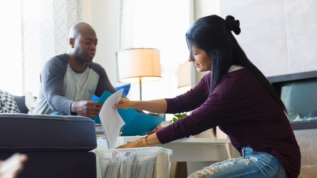 Couple filing paperwork at home