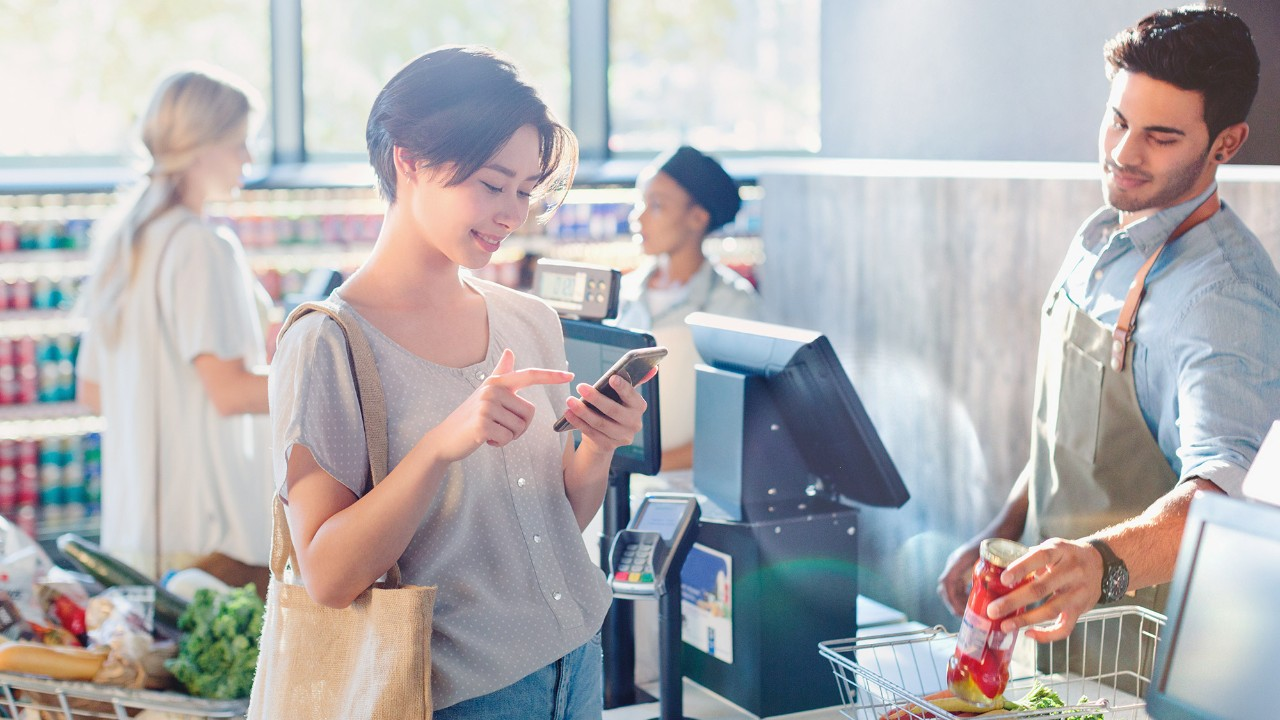 Woman using mobile phone at grocery store
