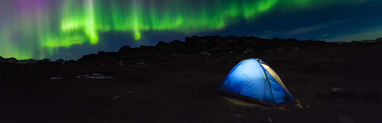 tent in mountains under northern lights