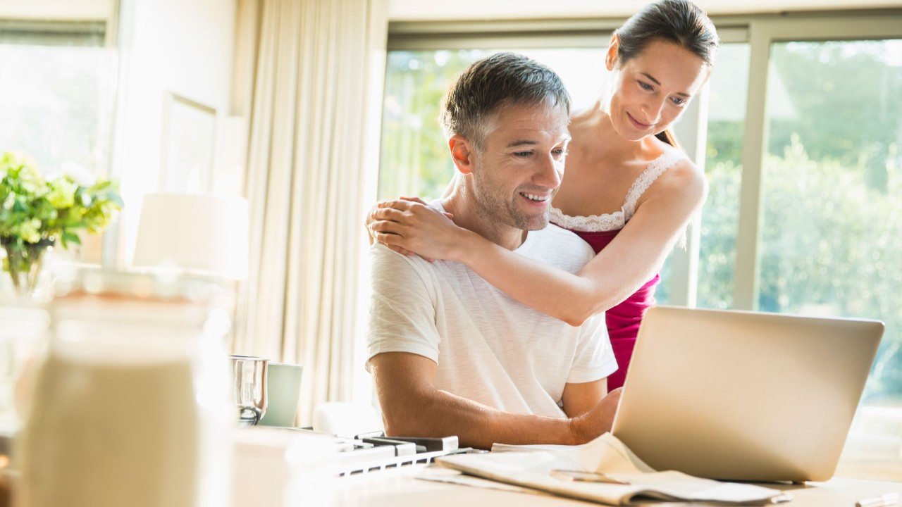 couple holding checking laptop